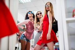 Низко-угол снял стильных блестящих подруг выбирая новые одежды и солнечные очки стоя представляющ перед Стоковое Изображение