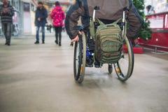 Никакая сторона не постарела неработающее, инвалид на, который катят стуле среди людей без инвалидности в моле рыночного местя Se стоковое фото rf