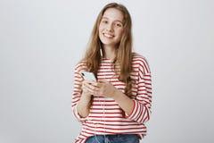 Никогда не выходит домой без хорошей музыки в наушники Портрет положительной довольной привлекательной девушки держа smartphone Стоковые Изображения RF