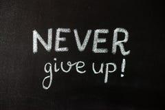 Никогда не дайте вверх, дело или обучите мотивационные слова стоковые фото
