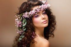 Нимфа. Прелестное чувственное брюнет с гирляндой цветков смотрит как ангел Стоковое Изображение RF