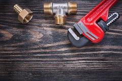 Ниппель шланга тройника равного латуни универсального гаечного ключа на деревянной предпосылке p Стоковое Фото