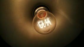 Нить внутри теплой электрической лампочки стоковое фото