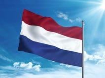 Нидерландский флаг развевая в голубом небе Стоковые Изображения