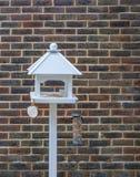 Новая белая таблица птицы устанавливала снова кирпичную стену Стоковое фото RF