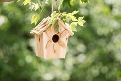 Новая деревянная смертная казнь через повешение Birdhouse на ветви дерева outdoors Стоковые Фото