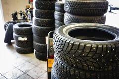 Новая зима утомляет в обслуживании гаража внутренности стогов автомобильном - изменяя колеса или автошины Стоковая Фотография