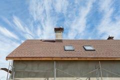 Новая крыша с окном в крыше, гонт толя асфальта и печной трубой Крыша с окнами мансарды Стоковые Фото