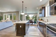 Новая кухня похваляется темные деревянные шкафы, большой остров стоковые фотографии rf