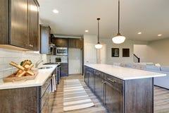 Новая кухня похваляется темные деревянные шкафы, большой остров стоковое фото rf