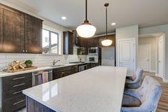 Новая кухня похваляется темные деревянные шкафы, большой остров стоковые изображения rf