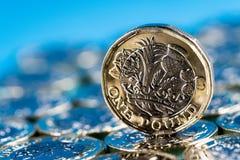 Новая монетка фунта введенная в Великобритании в 2017, фронте, стоя на слое монеток и на голубой предпосылке Стоковые Фото