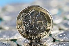 Новая монетка фунта введенная в Великобритании в 2017, фронте, стоя на слое монеток и на голубой предпосылке Стоковые Фотографии RF