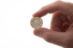 Новая монетка фунта держала в пальцах ` s человека Стоковая Фотография RF