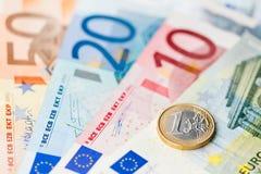 Новая одна монетка евро на банкнотах евро Стоковая Фотография