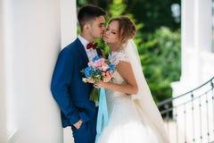 Новобрачные гуляют в зеленом парке с белыми столбцами Человек в костюме свадьбы хочет расцеловать девушку Женщина в свадьбе Стоковое фото RF