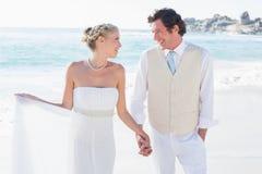 Новобрачные идя рука об руку и усмехаясь на одине другого Стоковое Изображение RF