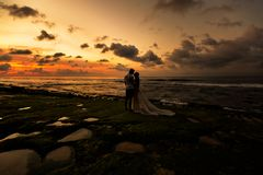 Новобрачные на пляже на заходе солнца стоковое изображение