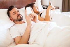 Новобрачные отправляя СМС в кровати Стоковая Фотография RF