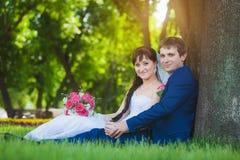 Новобрачные сидят на зеленой траве Стоковое фото RF