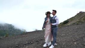 Новобрачные хипстера идя в течении ландшафта горы видеоматериал
