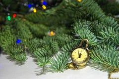 Новогодняя ночь, часы - медальон показывает 23 55 Скоро новое время на предпосылке зеленой рождественской елки стоковая фотография rf