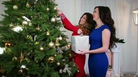 Новогодняя ночь, девушки подготавливают на праздник, украшают рождественскую елку, вид покрашенные игрушки рождества, золото акции видеоматериалы