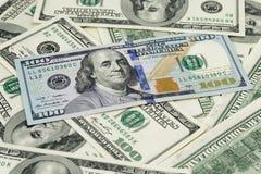 Новое 100 примечаний доллара на куче старых примечаний Стоковые Изображения
