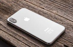 Новое iPhone x 10 на деревянной предпосылке, съемке студии стоковые фотографии rf
