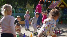 НОВОСИБИРСК, РОССИЯ - 16-ое августа 2017: В детском саде, женщина играя с детьми, активными играми outdoors акции видеоматериалы