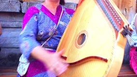 НОВОСИБИРСК, РОССИЯ - 15-ое июля 2015: женщина играет музыкальный инструмент сток-видео