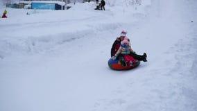 НОВОСИБИРСК, РОССИЯ - 3-ье января 2016: счастливые езды семьи и усмехаясь snowtube на снежных дорогах видеоматериал