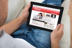 Новости персоны наблюдая на таблетке цифров Стоковые Фото