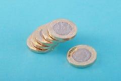 Новые британцы, Великобритания монетки одного фунта на голубой предпосылке Стоковое Изображение RF
