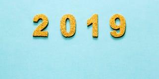 Новые Годы концепции 2019 разрешения номер года пробочки на свете - голубой предпосылке цвета стоковая фотография rf