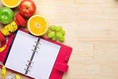 Новые Годы разрешений едят здоровую, теряют вес и соединяют спортзал, гантели для фитнеса с рулеткой, концепцией здорового образа Стоковые Фото