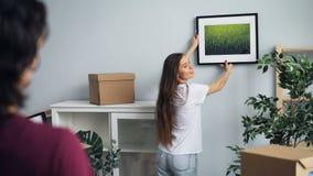 Новые домовладельцы девушка и парень выбирая место для изображения говоря и показывая жестами акции видеоматериалы