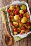 Новые картошки испекли с беконом, травами и концом-вверх томатов в a стоковое изображение rf