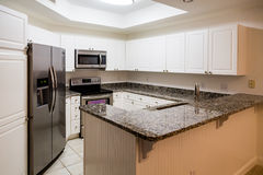 Новые нержавеющие приборы и счетчик гранита в белой кухне стоковые фотографии rf
