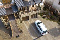 Новый белый автомобиль припаркованный в вымощенной подъездной дороге с зеленой лужайкой, декоративными кустами и загородкой кирпи стоковое изображение