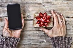 Новый Год дня рождения Крупный план smartphone в руках женщины и подарочной коробки с красным смычком на деревянном столе скопиру Стоковое фото RF