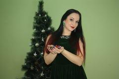 Новый Год Календарь 2018 девушка на Christmastree с красными подсказками волос держит шарики в его руках Зеленая предпосылка Стоковое фото RF
