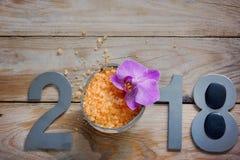 Новый Год 2018, курорт установил на деревянный стол, кокос и соль для принятия ванны, цветок орхидей и черные камни для горячего  Стоковое Изображение