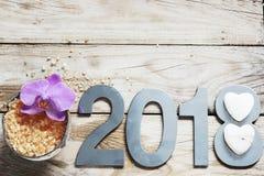 Новый Год 2018, курорт установил на деревянный стол, кокос и соль для принятия ванны, цветок орхидей и белые камни в форме сердца Стоковые Фото