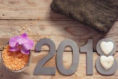 Новый Год 2018, курорт установил на деревянный стол, полотенце, кокос и соль для принятия ванны, цветок орхидей и белые камни в ф Стоковое Изображение
