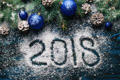 Новый Год 2018, написанный на муке и украшениях рождества, сосна разветвляет, конусы, голубые игрушки ` s Нового Года на деревянн Стоковая Фотография RF