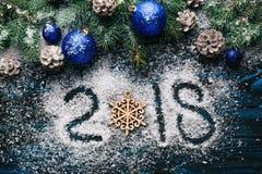 Новый Год 2018, написанный на муке и украшениях рождества, сосна разветвляет, конусы, голубые игрушки ` s Нового Года на деревянн Стоковое фото RF