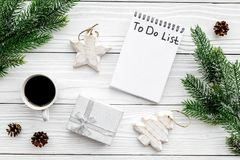 Новый Год планирования Тетрадь с для того чтобы сделать список около игрушек рождества, елевой ветви и pinecones на белой деревян Стоковая Фотография