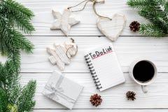 Новый Год планирования Тетрадь с для того чтобы сделать список около игрушек рождества, елевой ветви и pinecones на белой деревян Стоковое Изображение RF