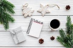 Новый Год планирования Тетрадь с для того чтобы сделать список около игрушек рождества, елевой ветви и pinecones на белой деревян Стоковые Фото